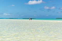 People walking through clear water over white sand South Pacific Island Royalty Free Stock Image