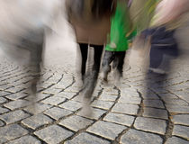 People walking on cobble stones Stock Images