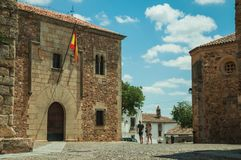People walking in a cobblestone alley amidst gothic buildings at Caceres royalty free stock photo