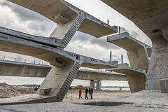 People walking in a constructionn site, under the piled units of Crown Princess Mary Bridge stock image