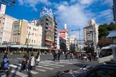 People walking cross road traffic midtown tokyo Stock Photo