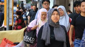 People walking crowded street in asian city. Muslim female tourists in traditional clothes walking on sidewalk of crowded street in asian city during vacation stock video