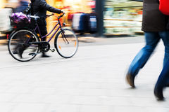 People walking and cycling in city in motion blur Stock Photos