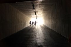 People are walking through dark tunnel Stock Photos