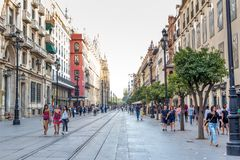 People walking during the day in a pedestrian street  near Cathedral in Seville, Spain. Famous landmark. People walking during the day in a pedestrian street Royalty Free Stock Photos
