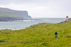 People walking a dog at Doolin Bay, Ireland. People walking a dog at Doolin Bay, county Clare, Ireland, with the Cliffs of Moher in the background Royalty Free Stock Photography