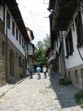 People walking down a cobblestone alley