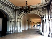 People walking down ornately carved archways in Balboa Park Royalty Free Stock Photography