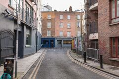 People walking down a small street with typical architecture of dublin