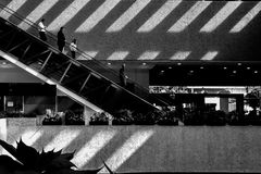 Pattern of shadows and light. People walking down stairs with a pattern of shadows and light Stock Images