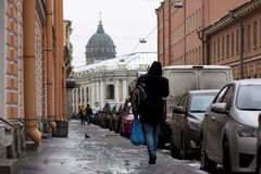 People walking down the street in the rain, cars parked along th Royalty Free Stock Photos