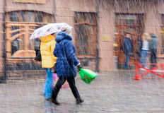 People walking down the street in a snowy winter. Day in motion blur Stock Photos