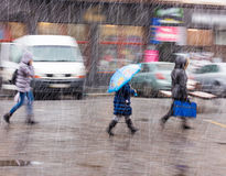 People walking down the street in a snowy winter day. In motion blur Royalty Free Stock Image