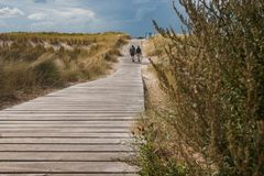 People walking in the dunes on the Dutch coast on a wooden deck royalty free stock images