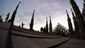 People walking on Duomo Cathedral roof terrace in Milan, Italy. The Gothic cathed stock footage