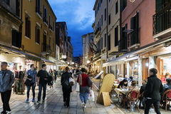 People walking and eating in the street called `Rio Tera Lista di Espagna` at dusk Stock Images