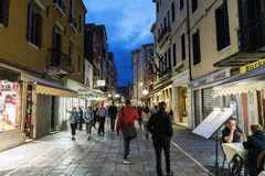 People walking and eating in the street called `Rio Tera Lista di Espagna` at dusk Royalty Free Stock Images
