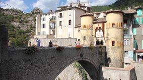 People walking in the entrance of the medieval city of Entrevaux, South of France stock footage