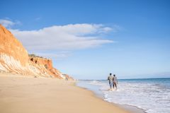People walking on Falesia Beach with beautiful cliffs, Albufeira. People walking on Falesia Beach with beautiful cliffs by Atlantic Ocean, Albufeira, Algarve Stock Image