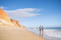 People walking on Falesia Beach with beautiful cliffs, Albufeira. People walking on Falesia Beach with beautiful cliffs by Atlantic Ocean, Albufeira, Algarve Stock Photo