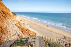 People walking on Falesia Beach with beautiful cliffs in Algarve. People relaxing on Falesia Beach with beautiful cliffs by Atlantic Ocean, Albufeira, Algarve Royalty Free Stock Photography
