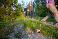 People Walking On Footpath By Lit Tealight Candle In Forest. Business people walking on footpath by lit tealight candle in forest during hiking Stock Photography