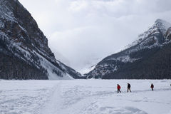 People walking on the frozen Lake Louise in winter. Three people walking on the frozen Lake Louise in winter stock photos