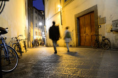 People walking in a historic street. In Florence at night, Italy Stock Photography