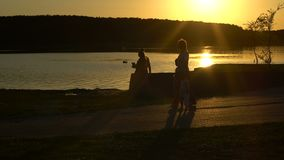 People are walking on the lake on the sunset. People are walking on the lake in the evening on the sunset stock footage