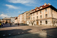 People walking in long shadows of sunny day in the center of polish city Stock Image