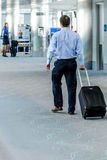 People walking with luggage in airport Stock Images