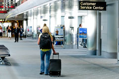 People walking with luggage in airport Stock Image