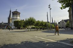 People walking by the Maritime Museum tower along a cobbled path in Dusseldorf, Germany. People walking by the Maritime Museum tower along a cobbled path in stock images