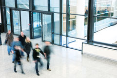 People Walking in Modern Office Building, Motion Blur. A commuter in motion indoors Royalty Free Stock Photo