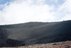 People walking on Mount Etna, active volcano on the east coast of Sicily, Italy royalty free stock image