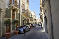 People walking in narrow alley in Syracuse on Ortigia island, Sicily, Italy stock image