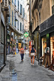 People walking on a narrow paved alley in Genoa Stock Images