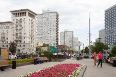 People walking near flower bed 20.08.2018. MOSCOW, RUSSIA - AUGUST 20, 2018: People walking near flower bed in Novy Arbat street. This street is located in the Stock Photo