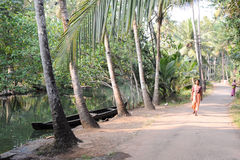 People walking near a river of the backwaters at Kollam Stock Image