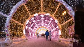 People walking through the New Year and Christmas holidays light tunnel in the city center in Moscow. Time lapse, Russia stock footage