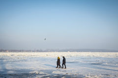 People walking next to the frozen Danube in Belgrade, Serbia, due to an exceptionally cold weather. A period of exceptionally cold and snowy winter weather in Royalty Free Stock Photo