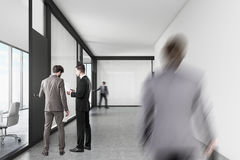 People walking in an office corridor with white and glass walls. People are walking in an office corridor with white and glass walls. Black door is leading to a Stock Photos