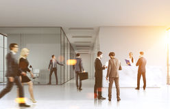 People walking in an office lobby. People are walking in an office with a gray and glass walls and a reception counter. 3d rendering, toned image Stock Images