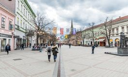 People walking on the old streets of Novi Sad city on the cloudy day with building architecture around.
