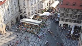 People walking Old Town Hall - Prague. PRAGUE - AUGUST 4: Aerial view of  Old Town Square - Clock's square and Jan Hus monument. People sitting and walking stock footage