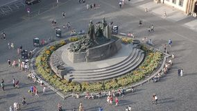 People walking Old Town Hall - Prague. PRAGUE - AUGUST 4: Aerial view of  Old Town Square - Clock's square and Jan Hus monument. People sitting and walking stock video footage