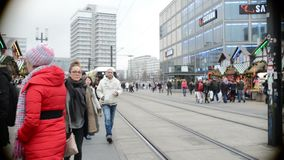 People walking over the Alexanderplatz christmas market in Berlin Mitte district. A tram is passing by. Berlin, Germany - December15, 2014 People walking over stock footage