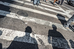 People walking over a cross walk on Fifth Avenue in New York City. Stylistic background concept cropped on pedestrians legs and focus on the road Stock Image