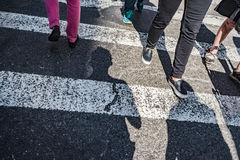 People walking over a cross walk on Fifth Avenue in New York City. Stylistic background concept cropped on pedestrians legs and focus on the road Royalty Free Stock Photo