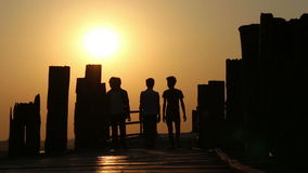 People Walking Over Wooden Bridge at Sunset 1 stock footage
